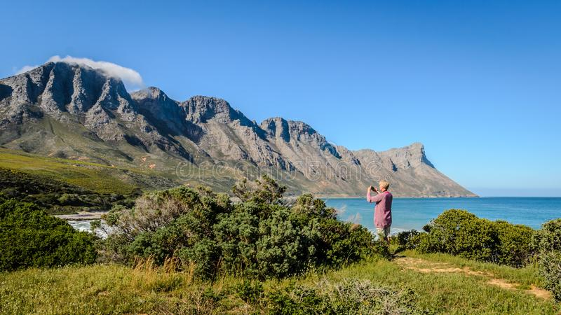 Kogelberg mountains nature reserve South Africa coast. Female tourist photographing scenic view in South Africa with phone camera on sunny day next to caost stock photo
