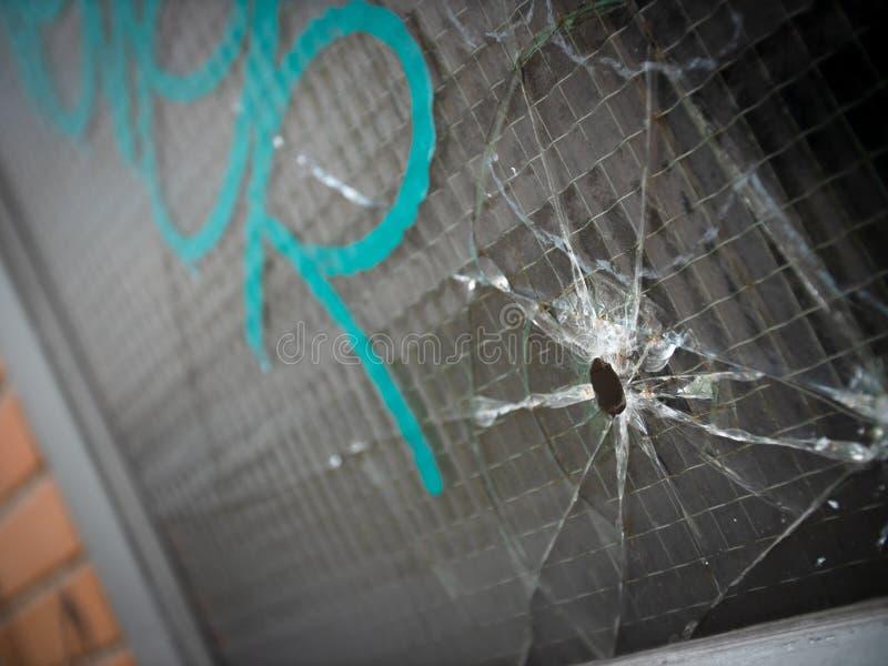Kogelgat en barsten in een versterkt venster stock fotografie