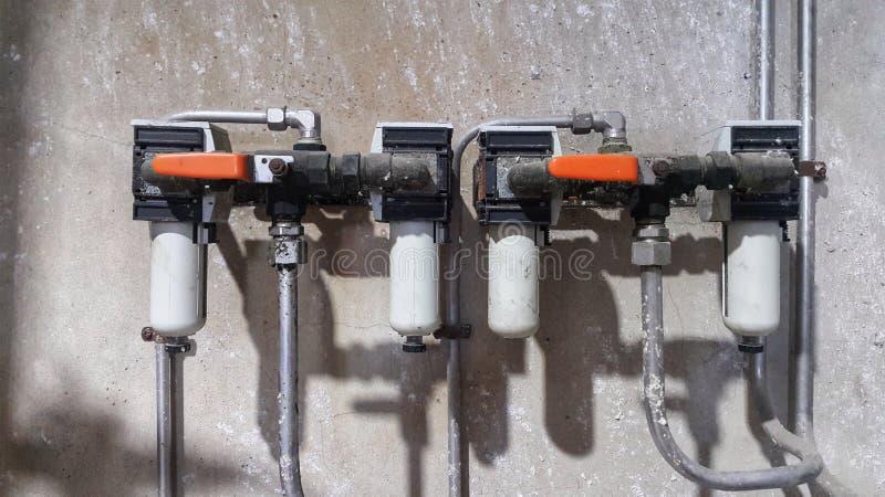 Kogelkleppen en het waterinstallatie van de filtercondensatie op cementmuur royalty-vrije stock foto