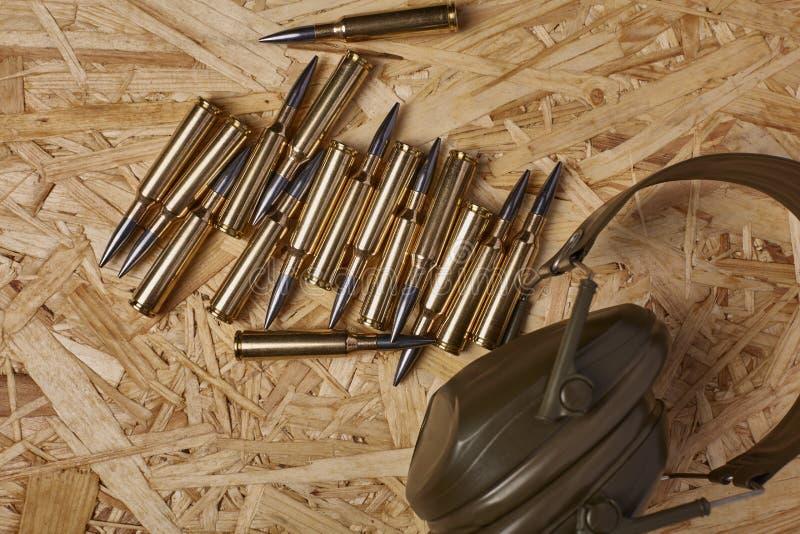 Kogels op houten textuur met hoorzittingsbescherming stock afbeeldingen