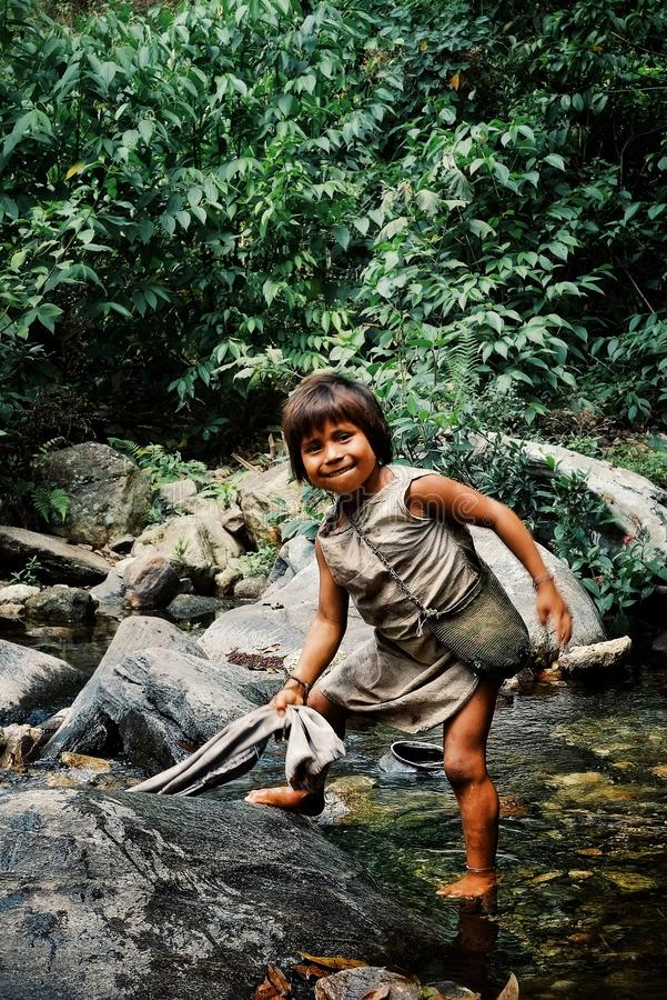 Kogi tribal kid doing laundry in the nearby stream close to their home. Santa Marta, Magdalena / Colombia - MARCH 10 2016 : kogi tribal kid doing laundry in the royalty free stock photo
