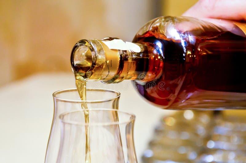 Kognak, der aus Flasche in Glas gie?t Alkoholiker, Getr?nk lizenzfreies stockbild