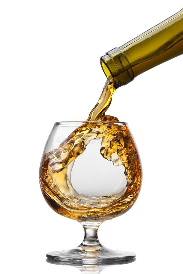 Kognak, der aus Flasche in Glas mit Spritzen auf Braun gießt lizenzfreies stockbild