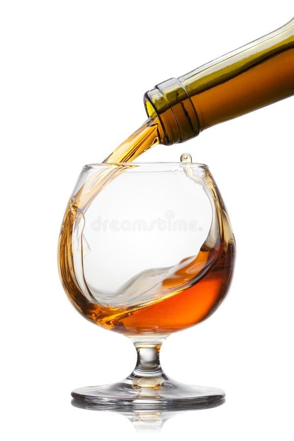 Kognak, der in Glas mit Spritzen auf weißem backgrou gießt stockfoto