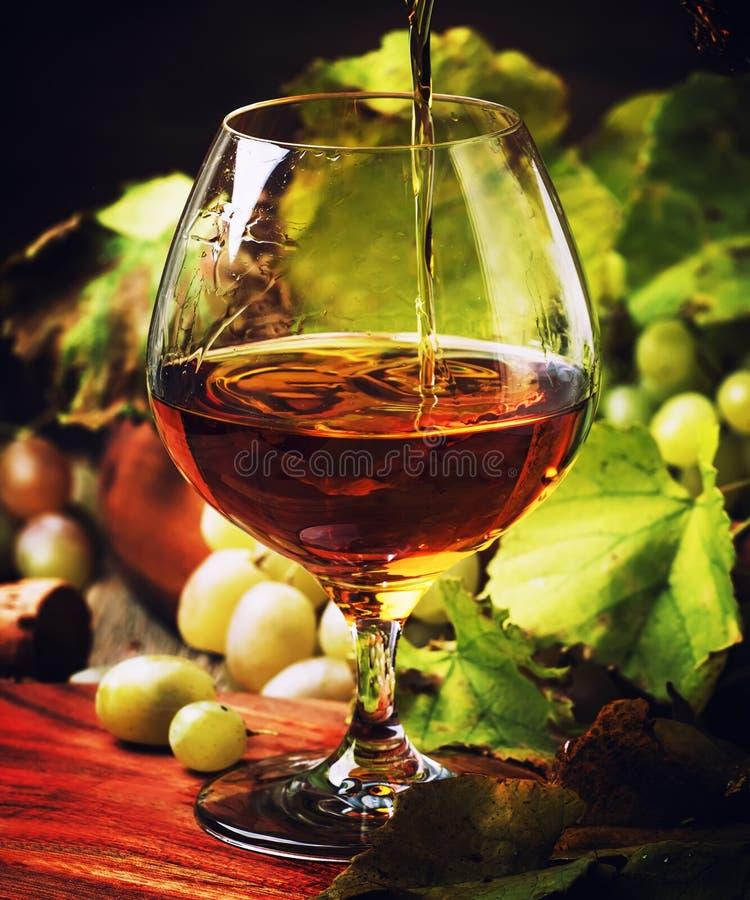 Kognak gießen herein Glas, Trauben und Rebe, Weinlese-hölzernen Hintergrund, stockbild