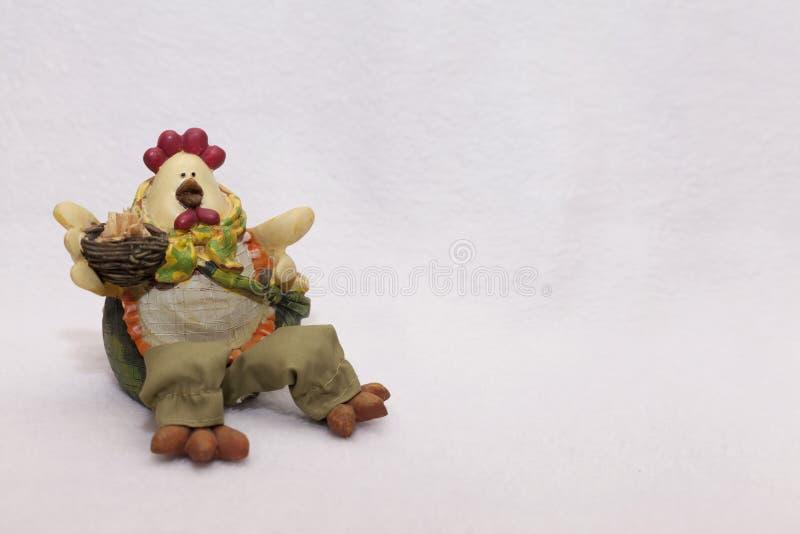 Kogut wielkanocny trzyma gniazdo z jajami, jest ubrany w elegancki jasny fartuch, spodnie i naszyjnik - a obraz royalty free