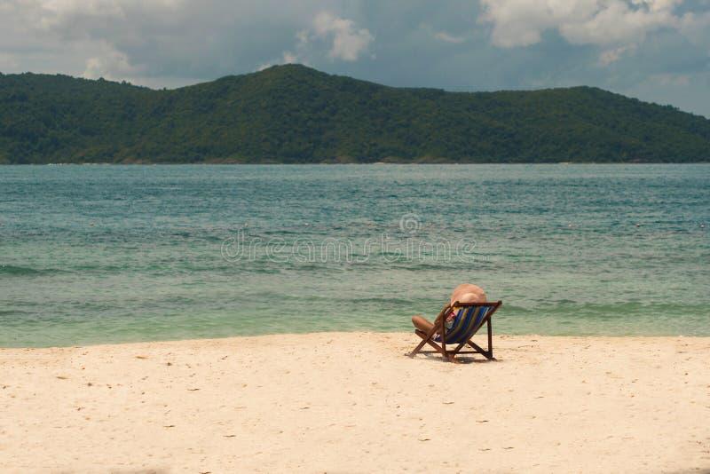 Koh он девушка a в шляпе отдыхает на пляже сидя в deckchair стоковое фото rf