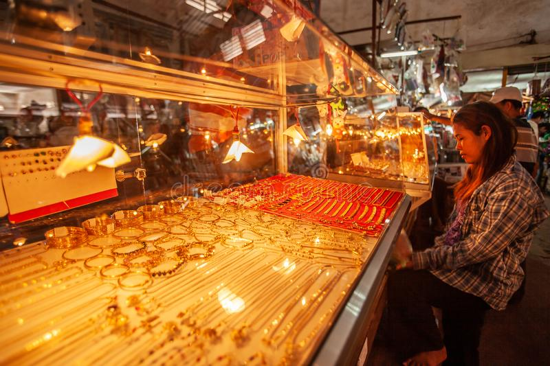 A khmer young girl chooses a piece of jewelry at local gold shop. Koh Kong Market, Koh Kong Province, Cambodia stock images