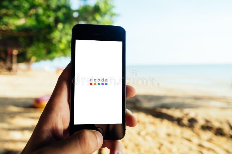 Koh Lanta, TAILANDIA - 13 marzo 2018: Primo piano dello schermo di iPhone con il LOGO di AGODA durante lo schermo di inizio fotografia stock libera da diritti