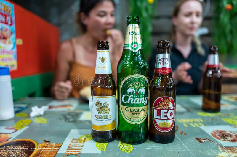 Koh Lipe, Thainald - February 20, 2019: Thai beers with caucasian girls in background. Koh Lipe, Thainald - February 20, 2019: Thai beers with caucasian girls royalty free stock image