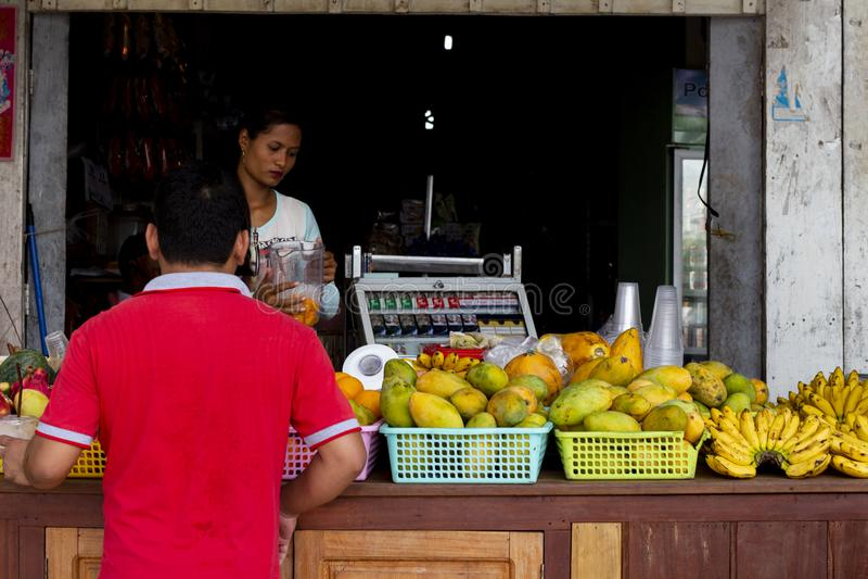 Koh Rong-eiland, Kambodja - 6 April 2018: de Khmer mens koopt tropisch fruit in lokale opslag Mango en banaan op lokale winkel stock afbeelding