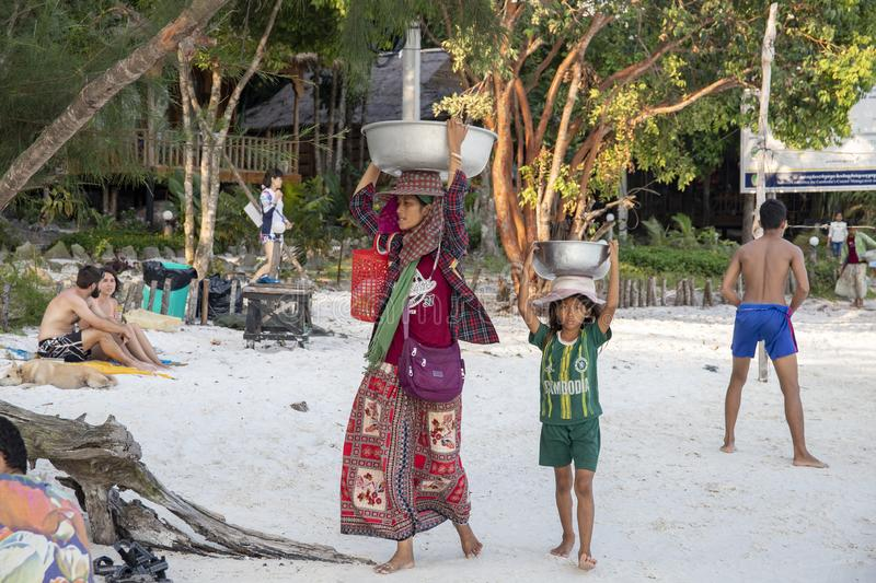 Koh Rong island, Cambodia - 6 April 2018: mother and child khmer selling fruits on beach. Tourist industry opportunities stock image