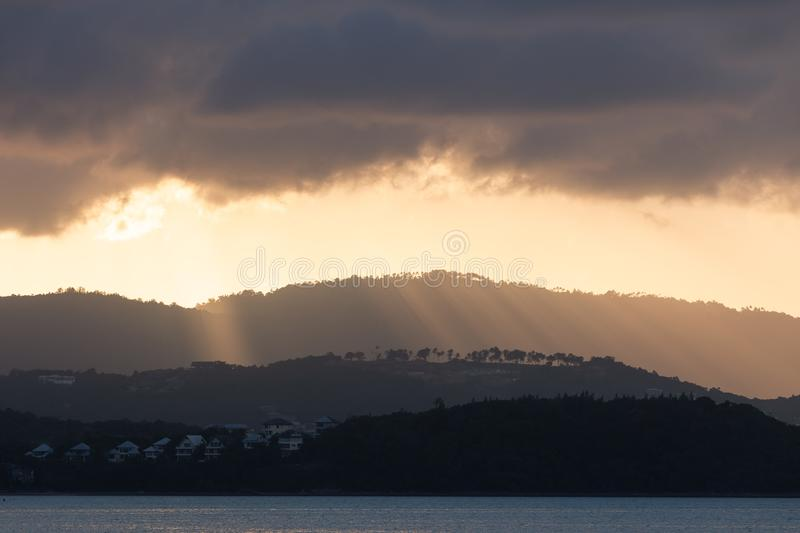 Koh Samui, Thailand During the sunset, the golden sunburst pond shines down on the mountain through clouds of light reflecting the royalty free stock photo