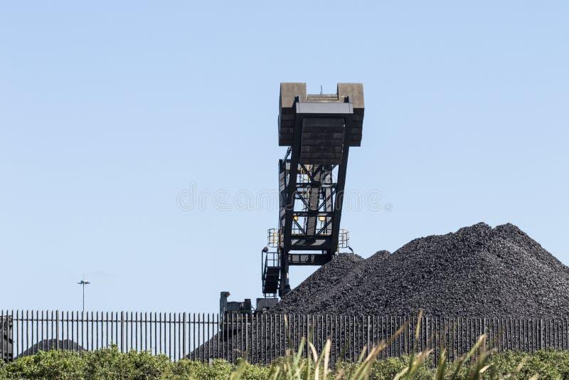 Kohle entleert mit Maschinerie auf einen Hintergrund des blauen Himmels lizenzfreies stockfoto