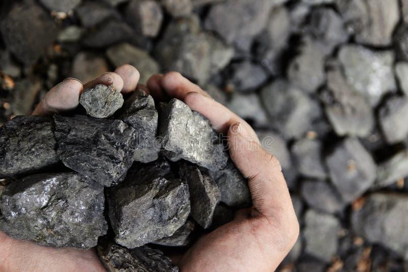 Kohlenbergmann in den Mannhänden des Kohlenhintergrundes Kohlenbergbau oder e stockfotografie