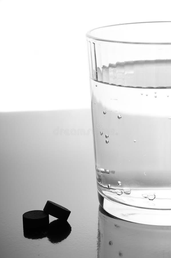 Kohletabletten und Glas Wasser stockfotografie
