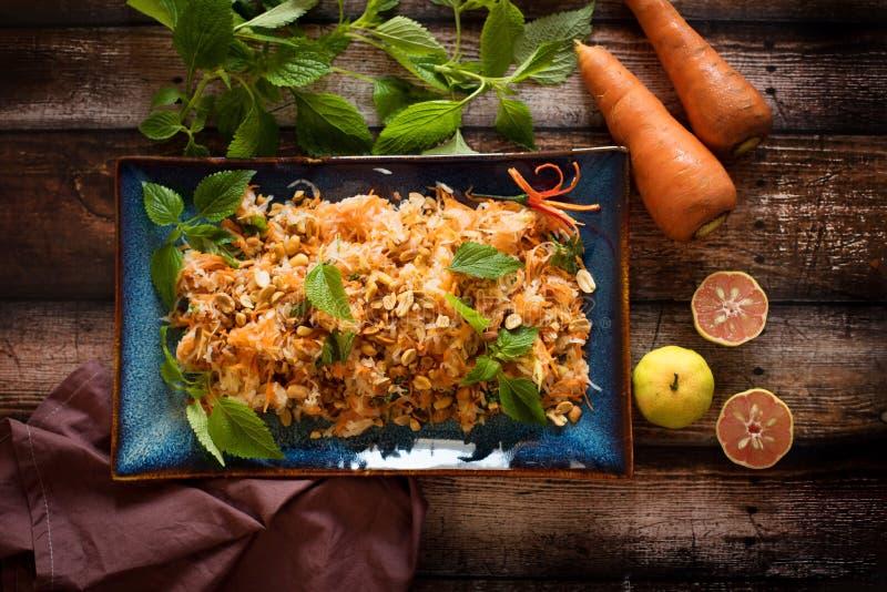 Kohlrabi-Karotten-Salat mit Erdnüssen, Zitrone und Kräutern stockbilder