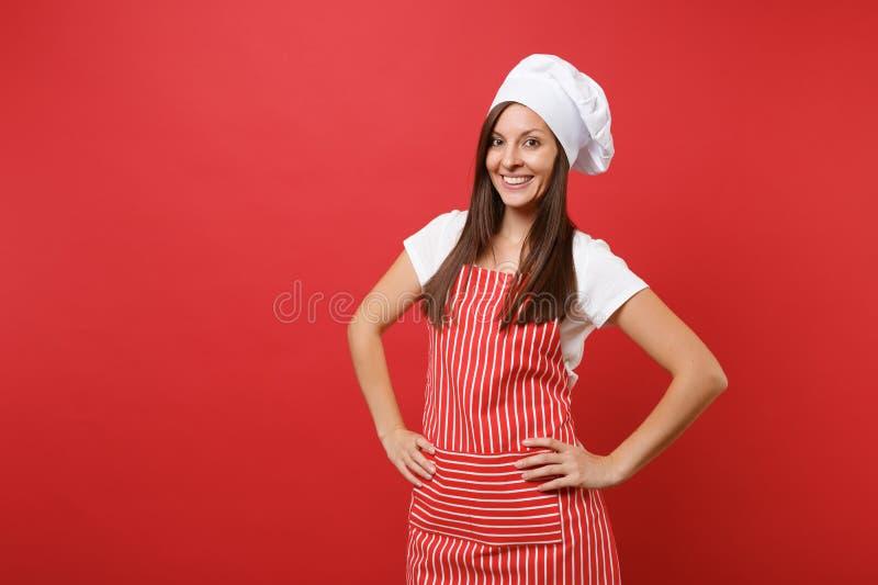 Kok of bakker van de huisvrouwen de de vrouwelijke chef-kok in gestreepte schort, witte t-shirt, toque chef-kokshoed die op rode  royalty-vrije stock afbeelding