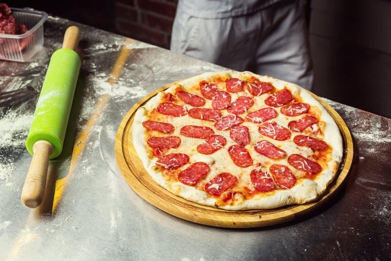 Kok Chef die heerlijke pizza bij het restaurant, close-up maken stock afbeeldingen