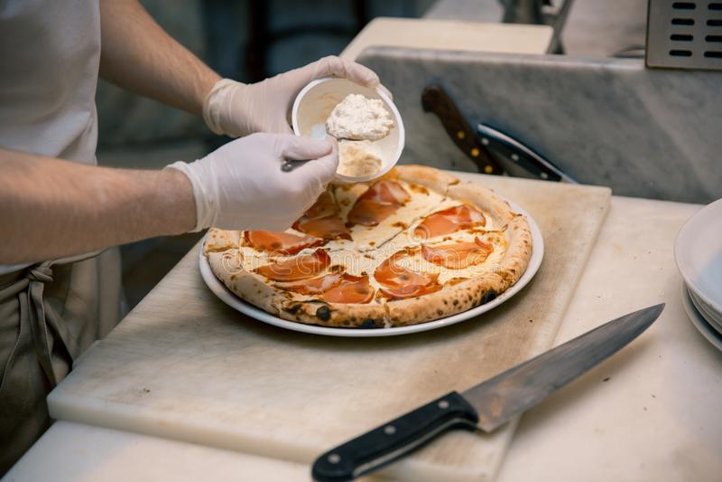 Kok in de keuken die de ingrediënten op de pizza zetten Pizzaconcept Productie en levering van voedsel royalty-vrije stock foto's