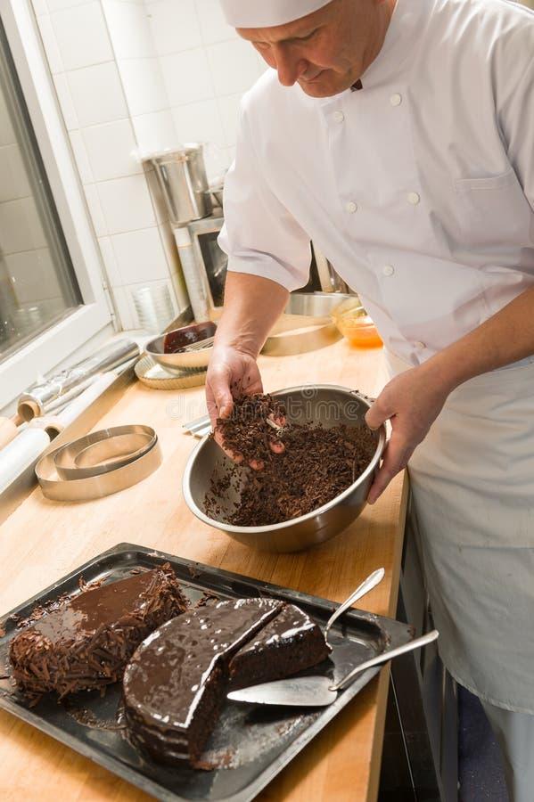 Kok die de cake van de chocoladesaus in keuken toevoegen stock fotografie