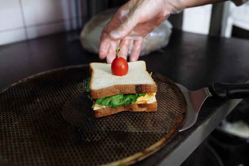 Kok die in polyethyleenhandschoenen een sandwich op een witte raad maken stock afbeelding