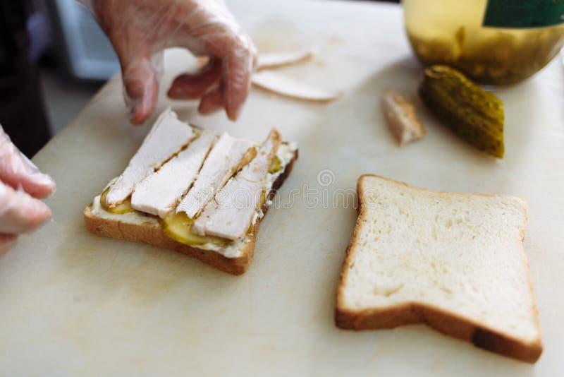 Kok die in polyethyleenhandschoenen een sandwich op een witte raad maken stock foto's