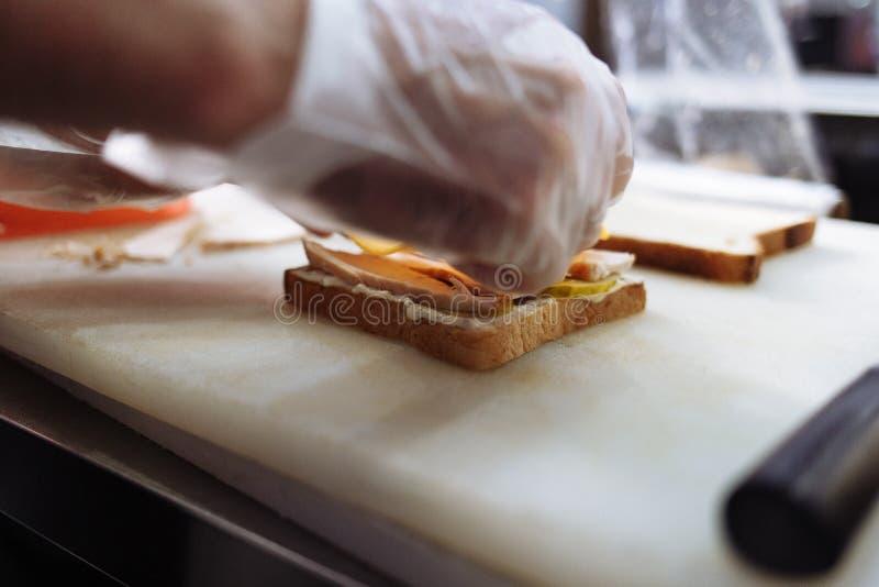 Kok die in polyethyleenhandschoenen een sandwich op een witte raad maken royalty-vrije stock afbeeldingen