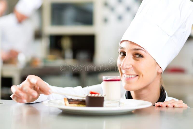 Kok, gebakjechef-kok, in hotel of restaurantkeuken stock afbeelding