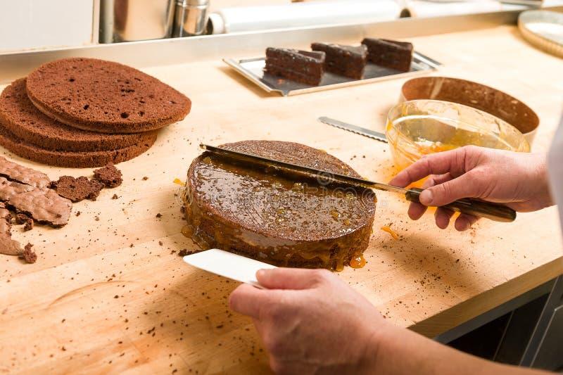 Kok het uitspreiden saus op cake in keuken royalty-vrije stock afbeelding