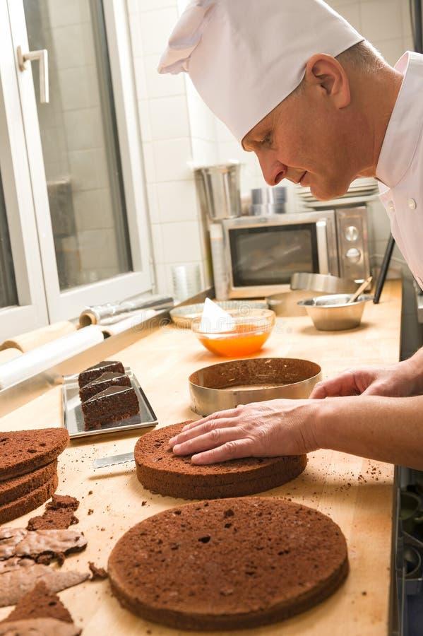 Kok in keuken het snijden de lagen van de chocoladecake stock afbeeldingen