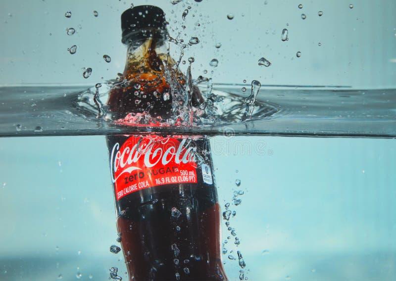 Koka-kola butelki chełbotanie w wodę obrazy stock