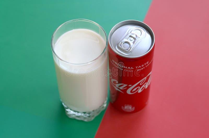 Koka-kola czerwona blaszana puszka i filiżanka świeży mleko na tle czerwieni i zieleni ukazujemy się fotografia stock