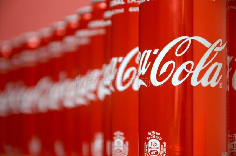 koka-kola logo drukujący na aluminiowych puszkach i umieszczający na centrum handlowe stole zdjęcie stock