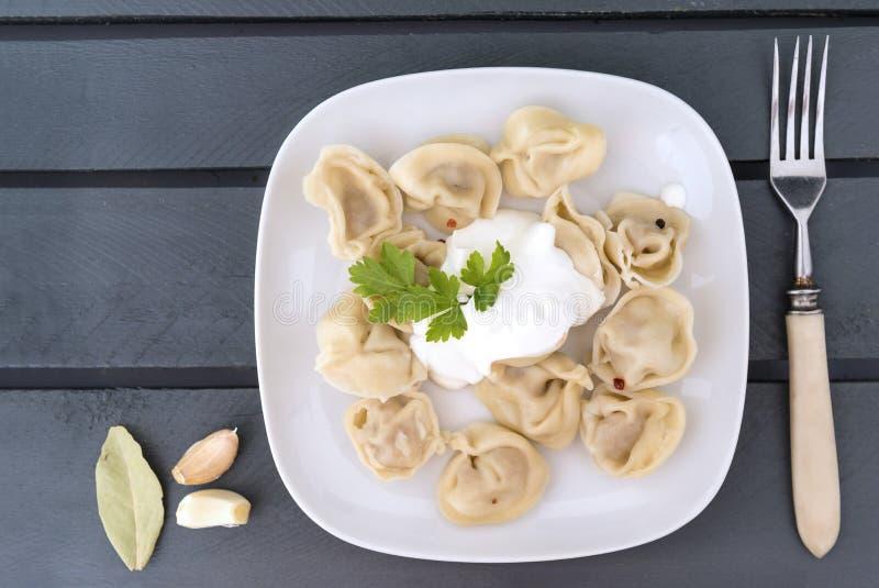 Kokade klimpar med gräddfil och örter på en vit platta, gaffel, vitlök, lagerblad på en trägrå bakgrund, bästa sikt royaltyfria foton