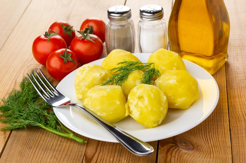 Kokade potatisar, dill i platta, saltar och pepprar, grönsakolja, tomater, gaffel på trätabellen fotografering för bildbyråer