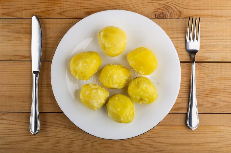 Kokade potatisar i platta, kniv och gaffel på tabellen Top beskådar fotografering för bildbyråer