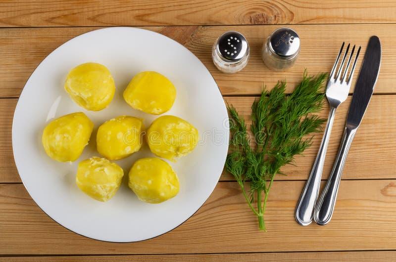 Kokade potatisar i platta, kniv och gaffel, saltar shaker, pepparshaker, dill på tabellen Top beskådar fotografering för bildbyråer