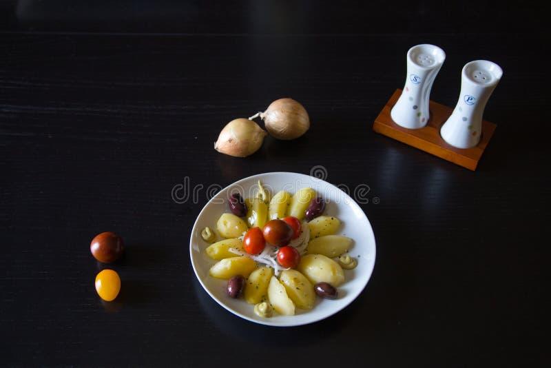 Kokade potatisar islolated med den organiska svarta oliv och löken fotografering för bildbyråer