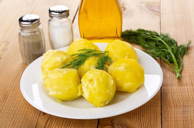 Kokade potatisar med dill i platta, saltar och pepprar, grönsakolja på trätabellen arkivfoto