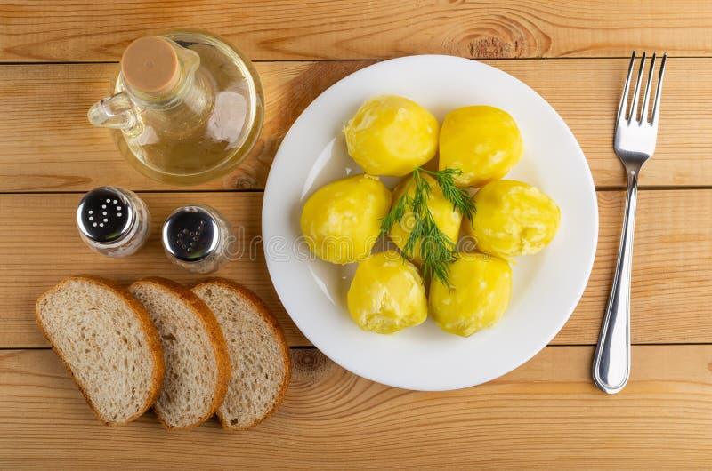 Kokade potatisar med dill i platta, saltar, peppar, grönsakolja, stycken av bröd, gaffel på tabellen Top beskådar royaltyfria bilder