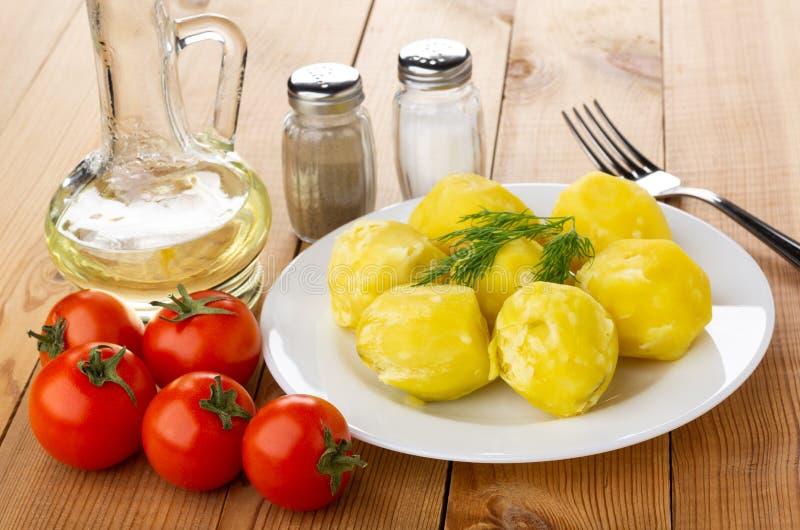 Kokade potatisar med dill i platta, saltar, peppar, grönsakolja, tomater, gaffel på tabellen royaltyfria bilder