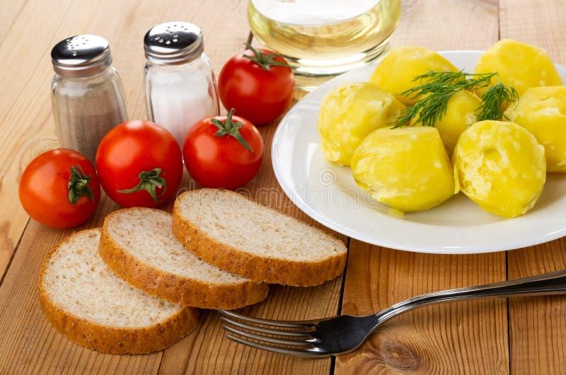 Kokade potatisar med dill i platta, saltar, peppar, grönsakolja, tomater, stycken av bröd, gaffel på tabellen arkivfoton
