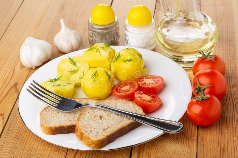 Kokade potatisar med tomater, bröd, gaffel i plattan, grönsakolja, saltar och pepprar, vitlök på tabellen royaltyfria bilder