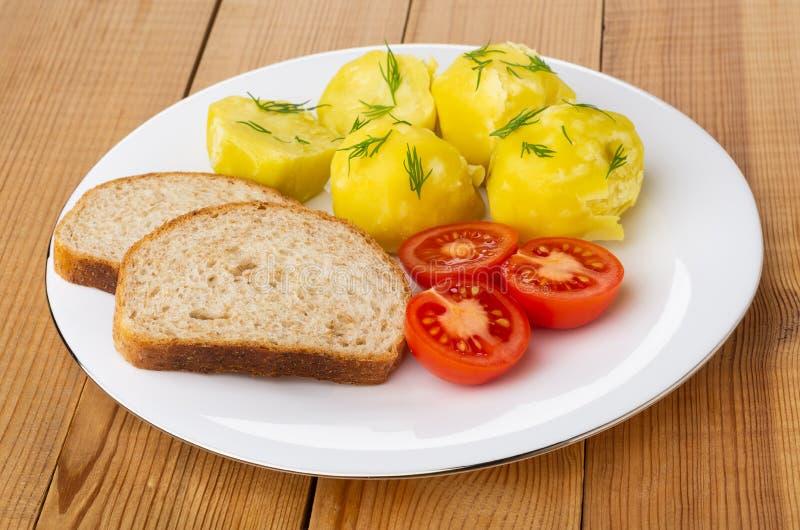 Kokade potatisar med tomater, bröd i den vita plattan på trätabellen arkivfoto
