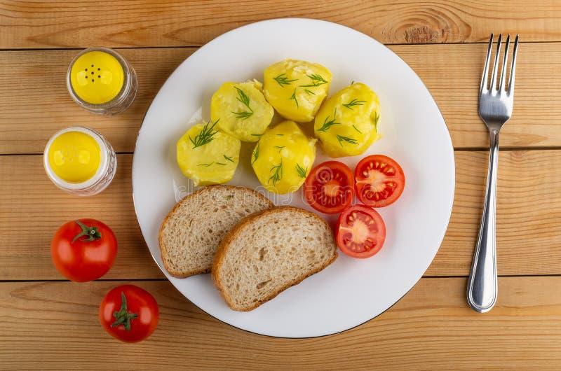 Kokade potatisar med tomater, bröd i platta, saltar och pepprar, gaffeln på tabellen Top beskådar arkivbild