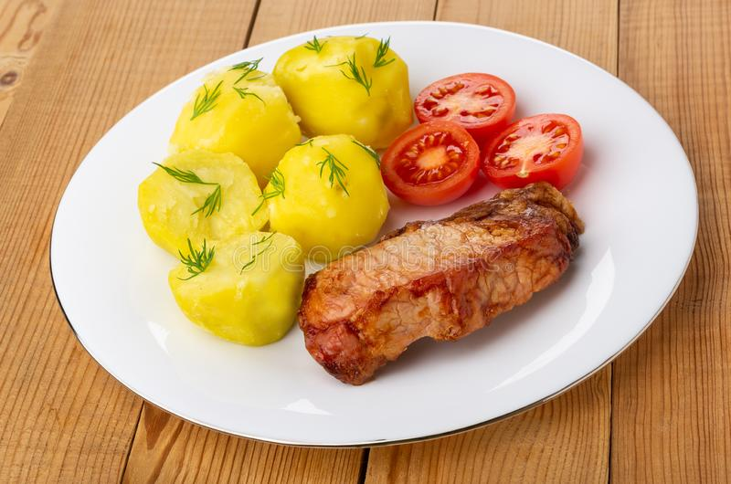 Kokade potatisar med tomater, stekt carbonnade i platta på trätabellen royaltyfria bilder