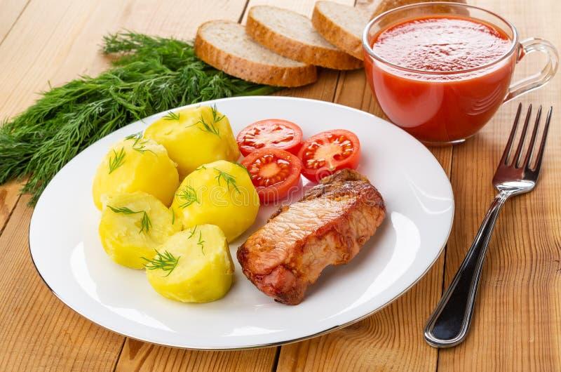 Kokade potatisar med tomater, stekt carbonnade i plattan, gaffel, kopp av tomatfruktsaft, stycken av bröd, dill på tabellen royaltyfri foto