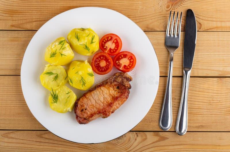 Kokade potatisar med tomater, stekt carbonnade i plattan, kniv, gaffel på tabellen Top beskådar arkivbilder
