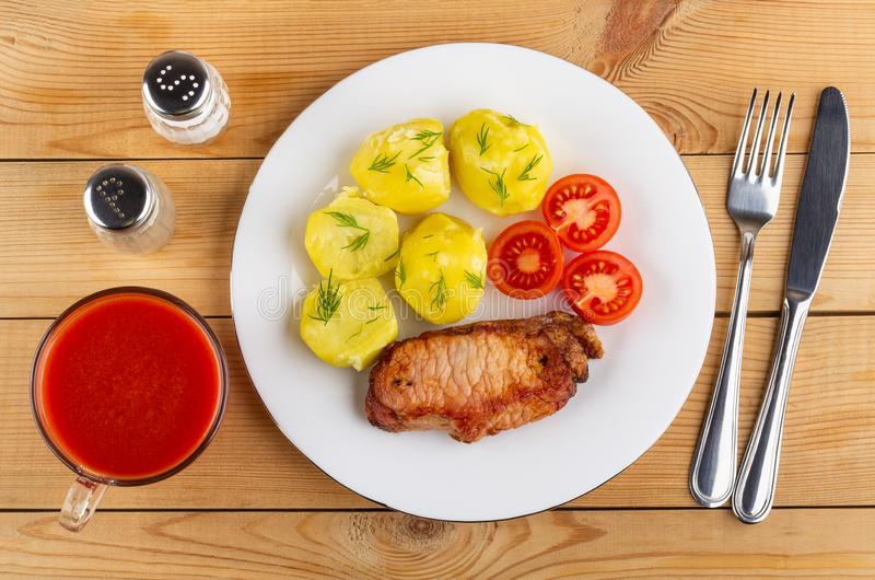 Kokade potatisar med tomater, stekt carbonnade i plattan, kniven, gaffeln, tomatfruktsaft, saltar, peppar på tabellen Top beskåda arkivfoton